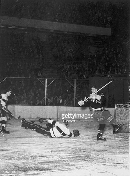 Canadian professional hockey player Bill Durnan goaltender for the Montreal Canadiens falls on the ice as he attempts to block a play by New York...