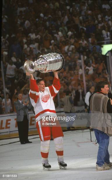 Canadian professional hockey player defenseman Larry Murphy of the Detroit Red Wings hoists the Stanley Cup over his head after they complete a sweep...