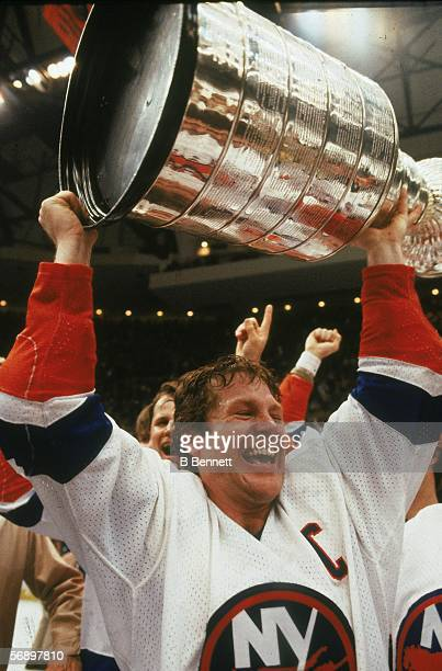 Canadian professional hockey player Denis Potvin of the New York Islanders hoists the Stanley Cup over his head as he celebrates their championship...