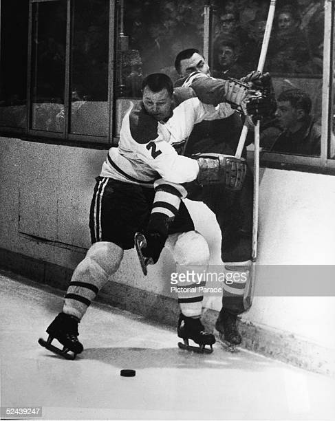 Canadian professional hockey player Doug Harvey of the Montreal Canadiens slams an opponent against the boards to keep him away from the puck, 1950s.