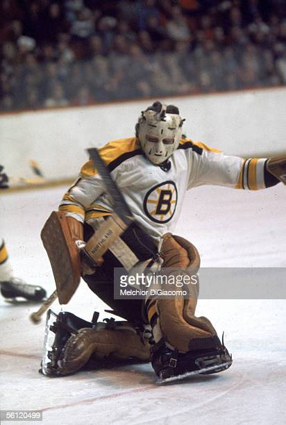 Canadian professional hockey player Ed Johnston, goalie for the Boston Bruins, kneels on the ice and attempts to block the puck during a game, 1970s.