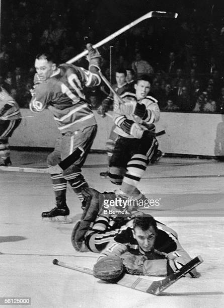 Canadian professional hockey player Ed Johnston goalie for the Boston Bruins deflects a puck shot by Bob Dillabough of the Toronto Maple Leafs as...