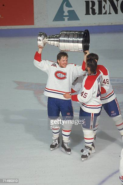 Canadian professional hockey player Gary Leeman right wing for the Montreal Canadiens hoists the Stanley Cup over his head as he celebrates their...