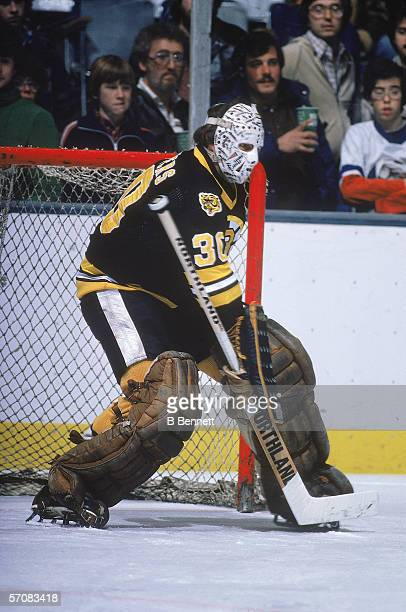 Canadian professional hockey player Gerry Cheevers of the Boston Bruins defends the goal on the ice during a road game, late 1970s.