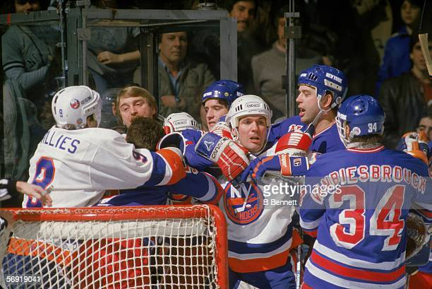 Canadian professional hockey player Gord Lane of the New York Islanders restrained by New York Ranger Willie Huber confronts Ranger gaolie John...