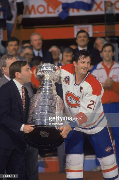 Canadian professional hockey player Guy Carbonneau center for the Montreal Canadiens accepts the Stanley Cup from American NHL commissioner Gary...