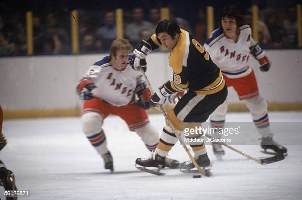 Canadian professional hockey player Johnny Bucyk of the Boston Bruins keeps the puck away from defensemen Ron Harris and Jim Neilson of the Rangers...
