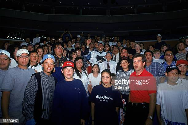 Canadian professional hockey player Jonathan Cheechoo stands in the bleachers with his family friends and other wellwishers from his hometown of...