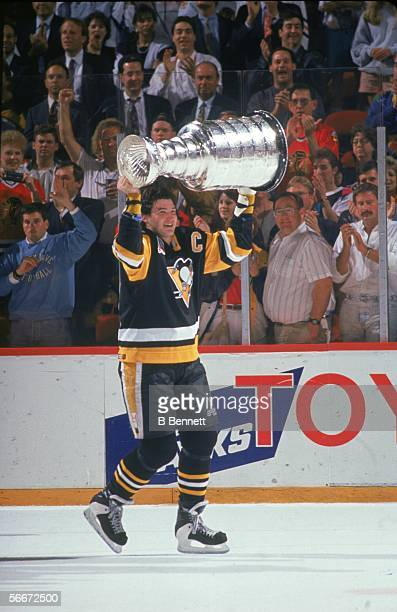 Canadian professional hockey player Mario Lemieux, forward for the Pittsburgh Penguins, hoists the Stanley Cup over his head and takes it for a...