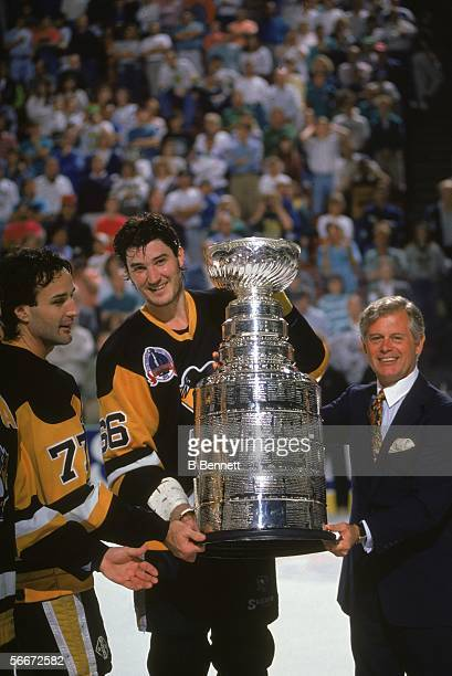 Canadian professional hockey player Mario Lemieux forward for the Pittsburgh Penguins teammate Paul Liffey and league president John Ziegler pose...