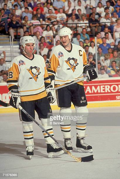 Canadian professional hockey player Mario Lemieux , forward for the Pittsburgh Penguins, talks to his teammate, American defenseman Gordie Roberts on...