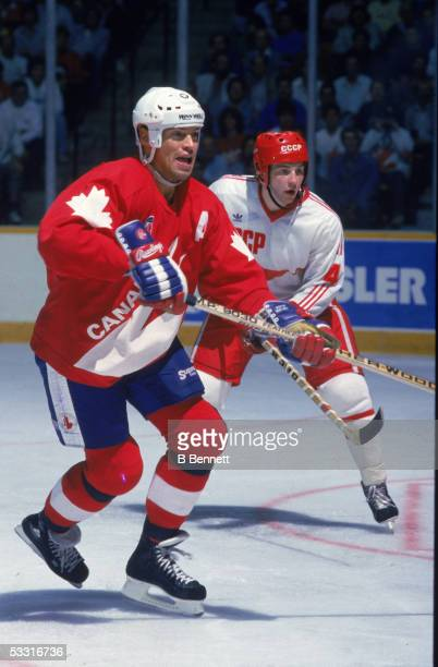 Canadian professional hockey player Mark Messier center for Team Canada prepares to swing as an opposing member from Team USSR stands by during the...