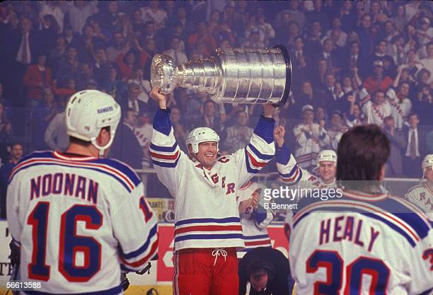 Canadian professional hockey player Mark Messier of the New York Rangers hoists the Stanley Cup championship award trophy over his head as teammates...