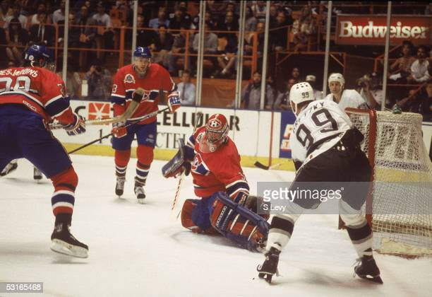 Canadian professional hockey player Patrick Roy goalie of the Montreal Canadiens makes a save while fallen on the ice against Wayne Gretzky of the...
