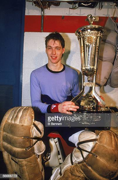 Canadian professional hockey player Patrick Roy, goaltender for the Montreal Canadiens, still wearing his knee pads sits near a locker room and holds...