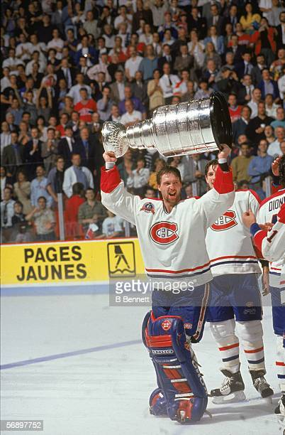 Canadian professional hockey player Patrick Roy of the Montreal Canadiens hoists the Stanley Cup over his head as he celebrates their championship...