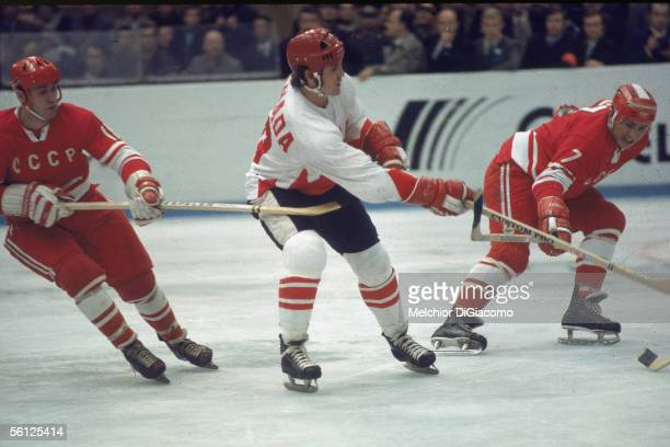 Canadian professional hockey player Paul Henderson , left wing for Team Canada, is flanked by two Soviet players during a game from the Summit...