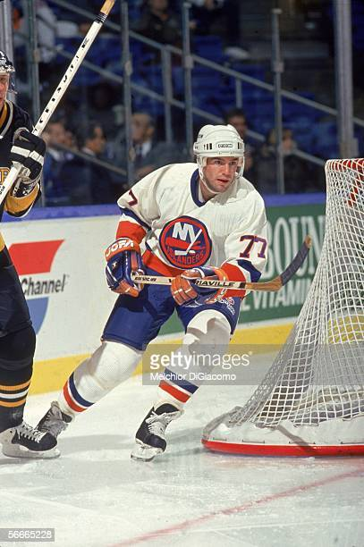 Canadian professional hockey player Pierre Turgeon center for the New York Islanders skates past the goal post during a game with the Pittsburgh...
