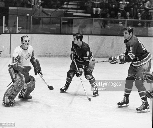 Canadian professional hockey player Roger Crozier goalie for the Detroit Red Wings defends the net against the advances of the two New York Rangers...