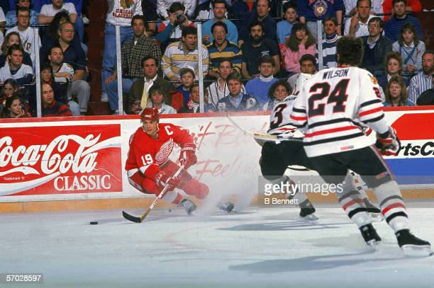 Canadian professional hockey player Steve Yzerman center for the Detroit Red Wings controls the puck while Canadian professional hockey players and...