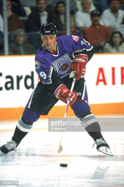Canadian professional hockey player Steve Yzerman center for the Detroit Red Wings plays with the puck on the ice during the NHL All Star Game San...