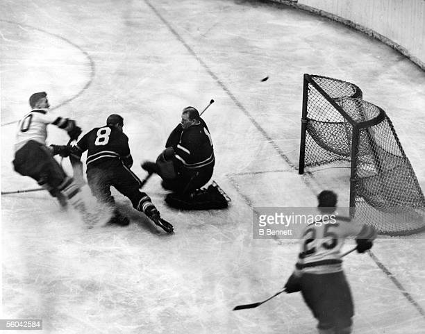 Canadian professional hockey player Walter 'Turk' Broda goalie for the Toronto Maple Leafs kneels in front of the goal post and attempts to block the...
