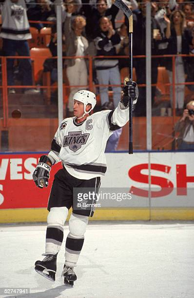 Canadian professional hockey player Wayne Gretzky of the Los Angeles Kings raises his stick in celebration during a game at the Western Forum...