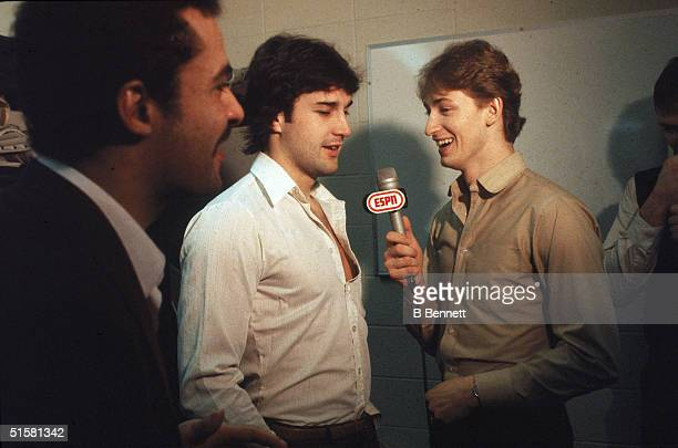 Canadian professional hockey player Wayne Gretzky pretends to interview teammate Paul Coffey while Grant Fuhr looks on, 1982.
