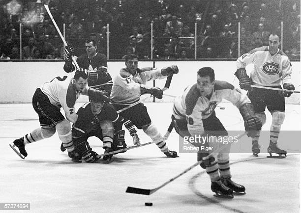 Canadian professional hockey players and Montreal Canadiens teammates Doug Harvey and Dickie Moore attempt to block an opposing player from the...