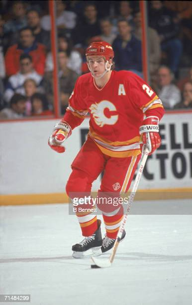 Canadian professional ice hockey player Al MacInnis of the Calgary Flames skates on the ice with the puck during an away game, 1990s. MacInnis played...