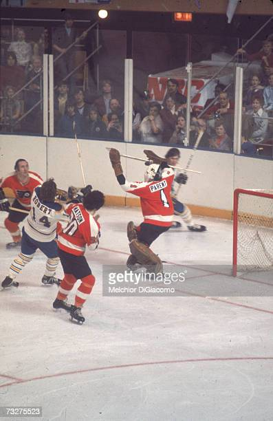 Canadian professional ice hockey player Bernie Parent , goalie of the Philadelphia Flyers, defends the goal amid a scuffle during an away game...
