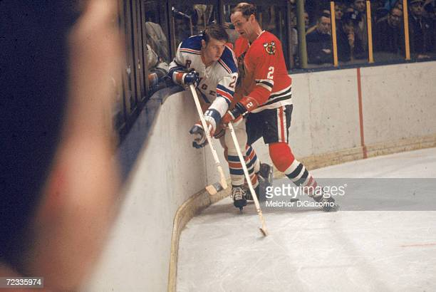 Canadian professional ice hockey player BIll White of the Chicago Blackhawks checks opponent Pete Stemkowski of the New York Rangers into the boards...
