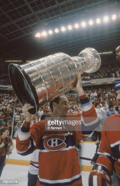 Canadian professional ice hockey player Bob Gainey of the Montreal Canadiens lifts the Stanley Cup over his head in celebration after his team won...
