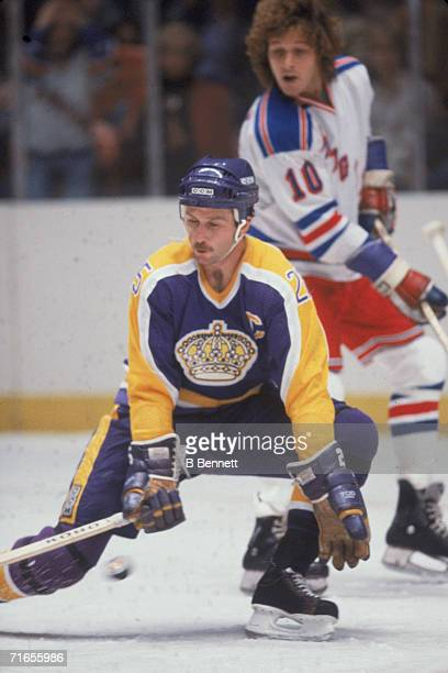 Canadian professional ice hockey player Dave Lewis of the Los Angeles Kings crouches down to block a shot as he skates on the ice and Ron Duguay of...