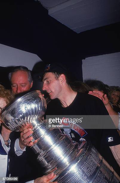 Canadian professional ice hockey player Denis Savard of the Montreal Canadiens gives a drink from the Stanley Cup to an old lady as he celebrates...