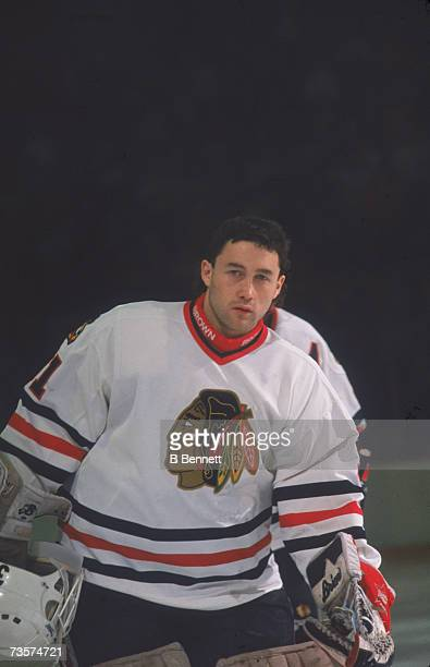 Canadian professional ice hockey player Ed Belfour goalie of the Chicago Blackhawks looks at the camera as he skates on the ice with his helmet in...