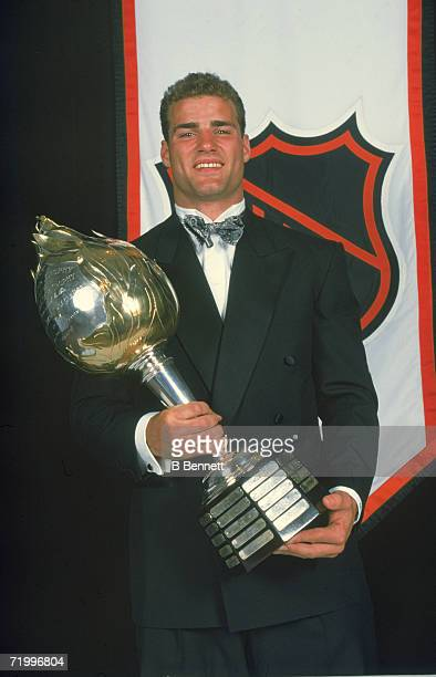 Canadian professional ice hockey player Eric Lindros wears a tuxedo as he holds up the Hart Memorial Trophy given to the League's most valuable...