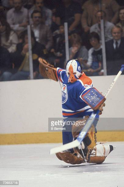 Canadian professional ice hockey player Grant Fuhr, goalie of the Edmonton Oilers, makes a save on the ice druing an away game, November 1981. Fuhr...