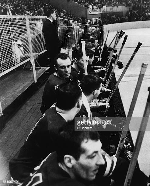 Canadian professional ice hockey player Harry Howell of the New York Rangers sits on the sidelines with teammates during a game early 1960s Howell...
