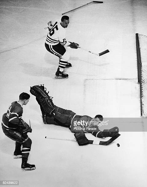 Canadian professional ice hockey player Jacques Plante goalie of the Montreal Canadiens dives to prevent a goal during a game against the Chicago...