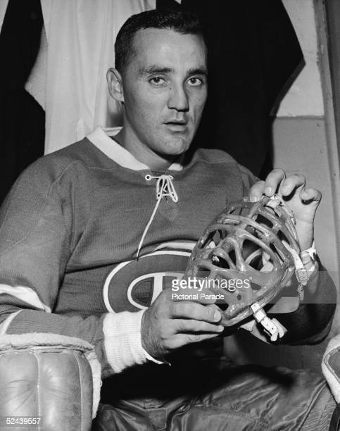 Canadian professional ice hockey player Jacques Plante goalie of the Montreal Canadiens sits in the locker room and shows his mask September 30 1960