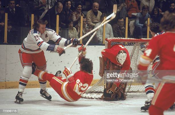 Canadian professional ice hockey player Pete Stemkowski of the New York Rangers checks a member of the Atlanta Flames onto the ice as they struggle...