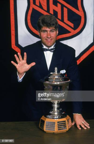 Canadian professional ice hockey player Ray Bourque of the Boston Bruins stands next to Norris Trophy for the NHL's best defenseman and signals that...