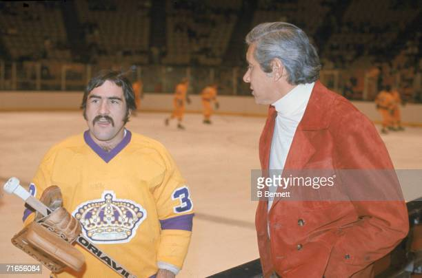 Canadian professional ice hockey player Rogatien 'Rogie' Vachon goalie of the Los Angeles Kings talks to a silverhaired gentleman on the sidelines...
