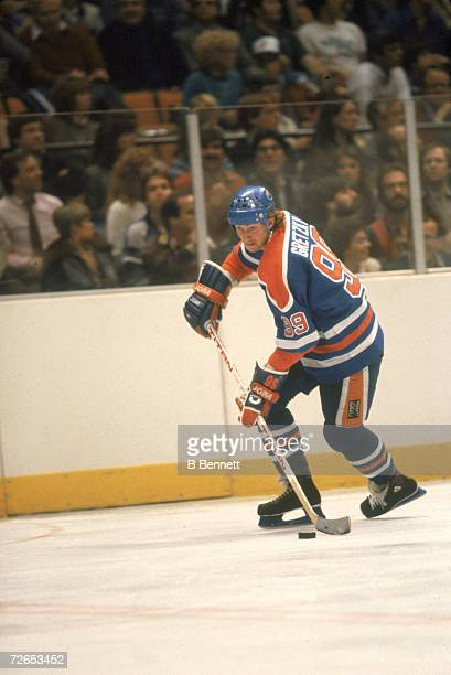 Canadian professional ice hockey player Wayne Gretzky of the Edmonton Oilers skates on the ice with the puck during an away game early 1980s Gretzky...