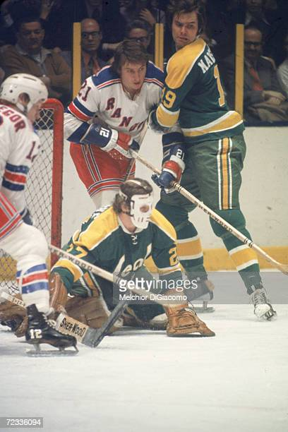 Canadian professional ice hockey players Bruce MacGregor and Pete Stemkowski of the New York Rangers struggle with opponents Gilles Maloche and Bert...