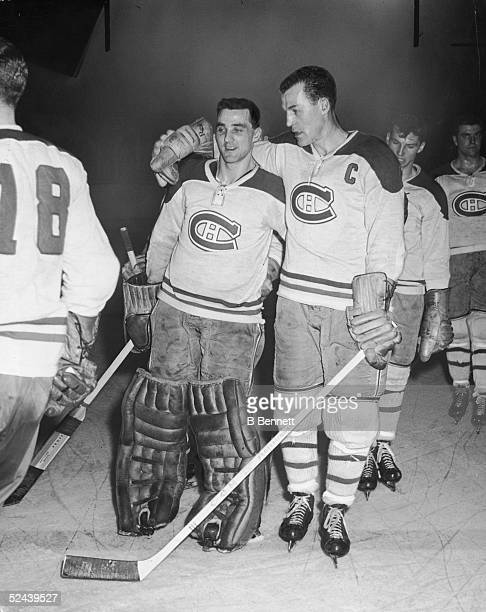 Canadian professional ice hockey players goalie Jacques Plante and Butch Bouchard of the Montreal Canadiens stand with their arms around each other...