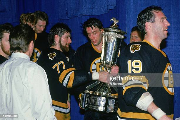 Canadian professional ice hockey players Ray Bourque and Cam Neely of the Boston Bruins lift the Prince of Wales Trophy which goes to the team which...