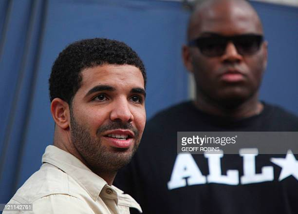 Canadian recording artist Drake watches as Serena Williams of the United States takes on Samantha Stosur of Australia in the final at the Rogers Cup...
