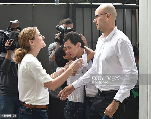 Canadian school administrator Neil Bantleman is met by his wife Tracy Bantleman as Indonesian teaching assistant Ferdinand Tjiong is hugged his wife...